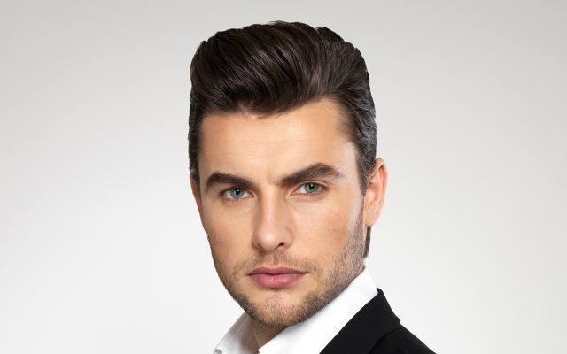 Ein Herren-Model mit einem modischen Haarschnitt schaut den Nutzer an