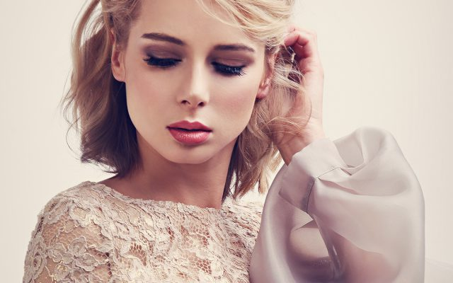 Beauty-Model mit einer stylischen Haarfrisur und perfektem Make-up neigt den Kopf zu Boden