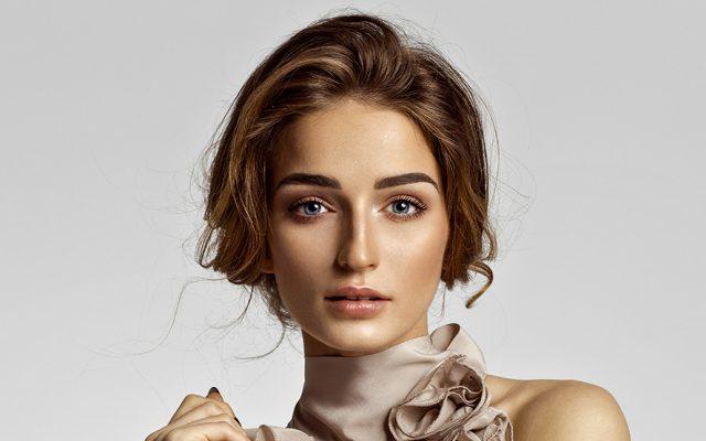Ein Damen-Model mit einem modischen Haarschnitt schaut den Nutzer an